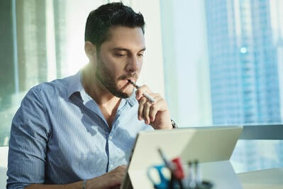Male employee vapes while working on the computer