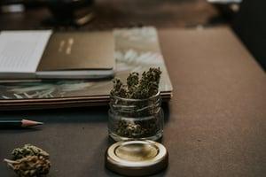 marijuana in a jar on a worker's desk