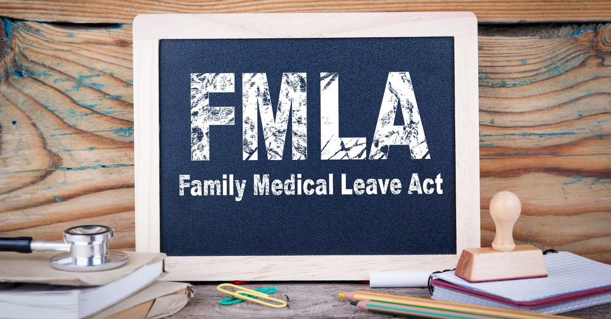 Small chalkboard with FMLA Family Medical Leave Act written on it is propped up on a desk