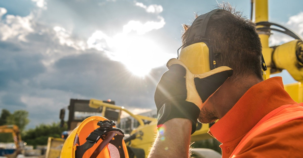 Construction worker places protective ear muffs over ears