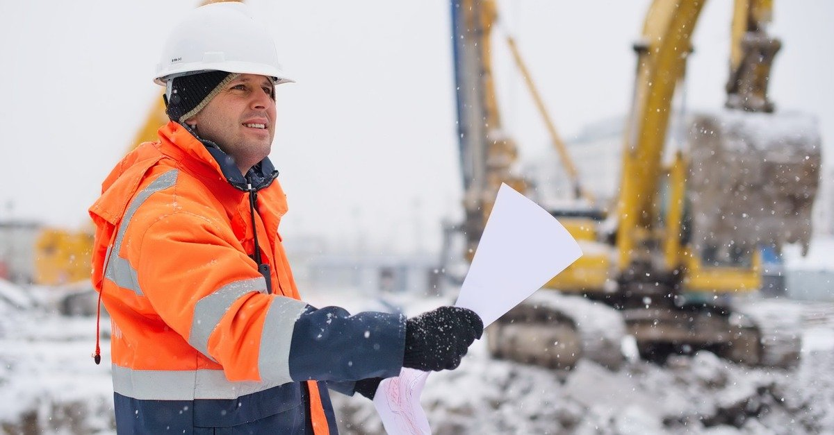 construction worker reads directions while it snows outside